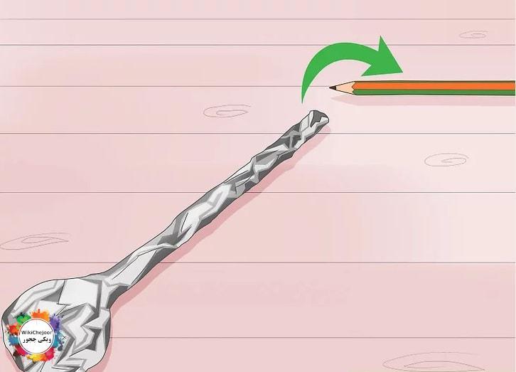 قرار دادن مداد در سوراخ توپ و پیچیدن ورق فلزی دور توپ